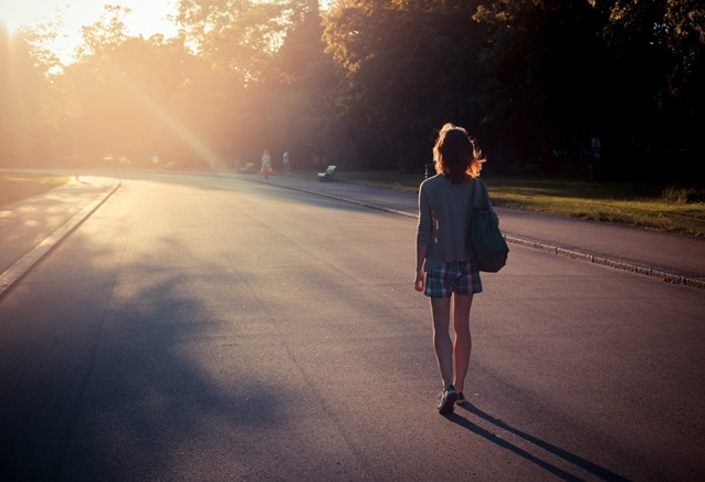 Woman walking into sunset in a park