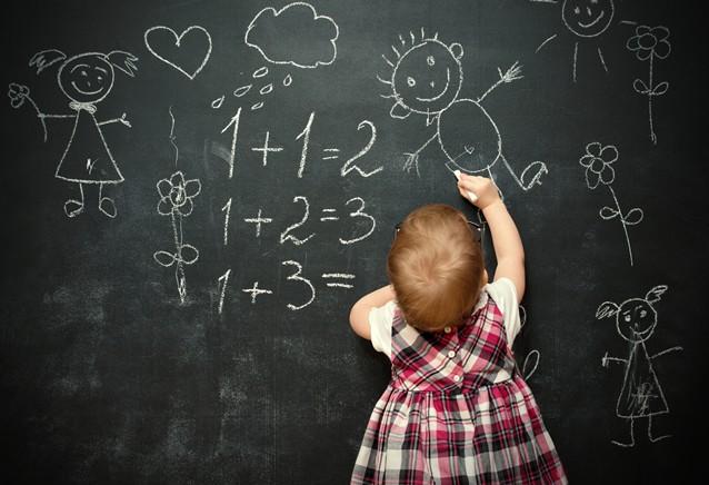 baby girl pupil draws a chalk on blackboard