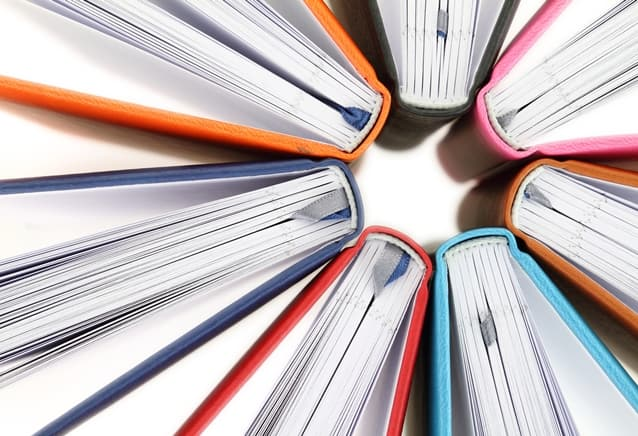 Top view of colorful books in a circle on white background