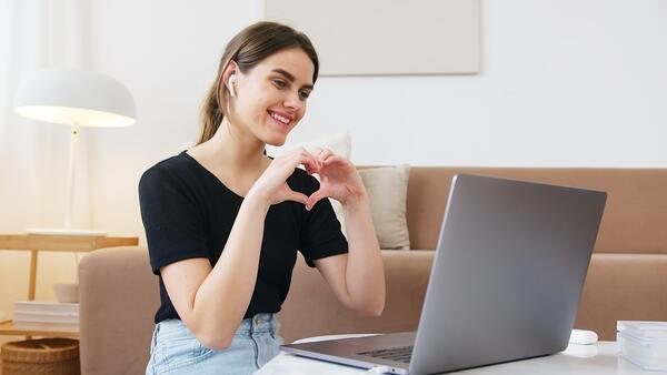 Mulher sorrindo e fazendo gesto de coração com as mãos em frente ao computador.