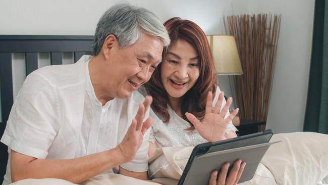 Casal sorrindo e acenando em frente a um tablet.