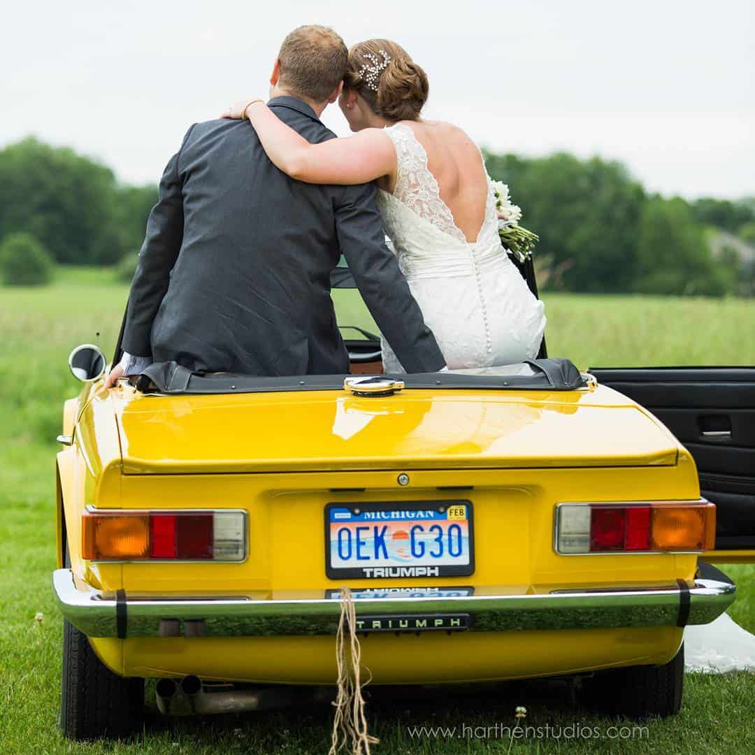 Noivo e noiva se abraçando sentados em um carro amarelo.