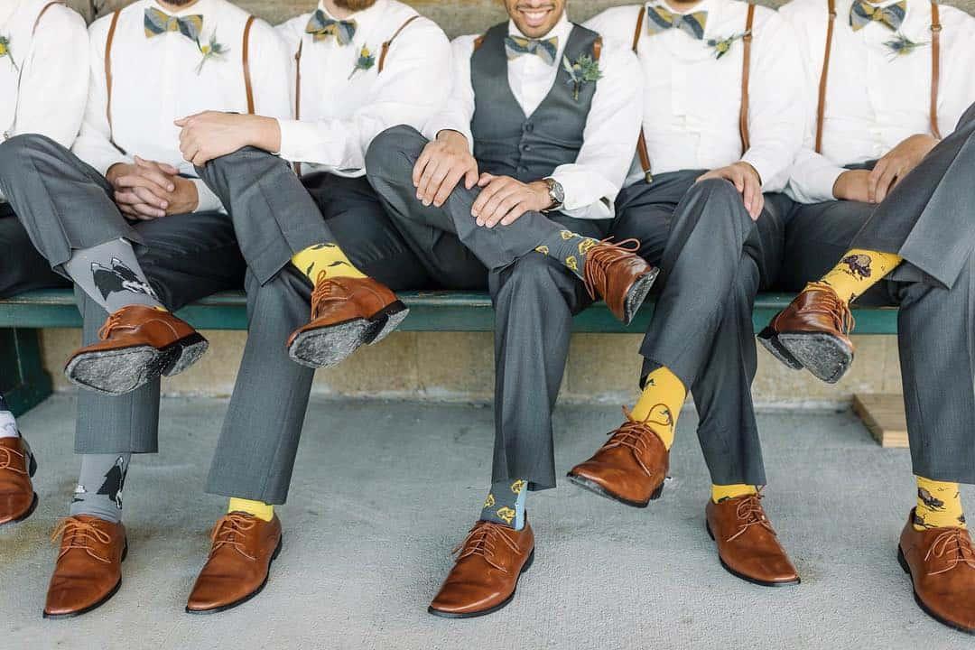 Padrinhos de casamento com terno cinza e meias amarelas.