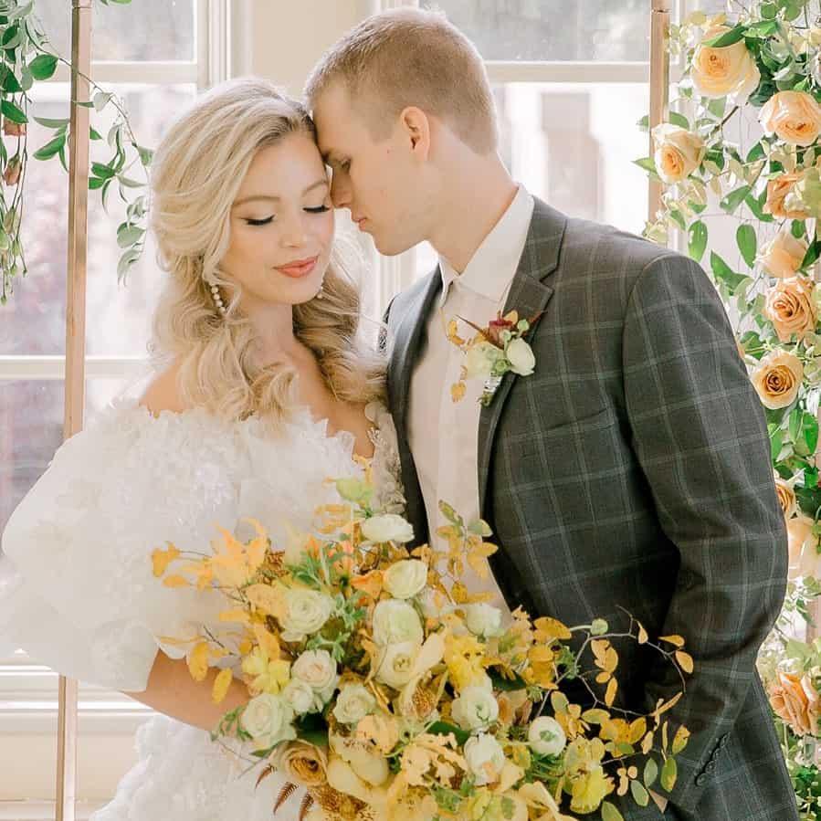 Noivos se abraçando com buquê de flores amarelas e noivo com traje cinza, na cor do ano 2021.