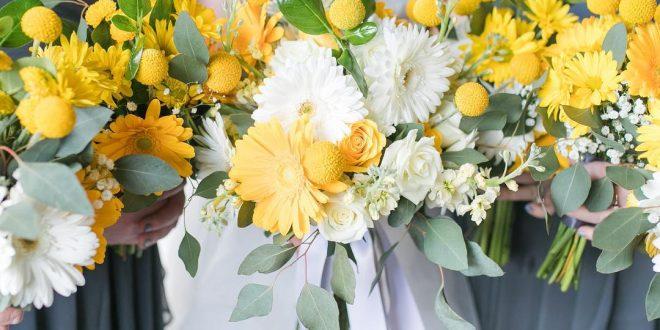 Noiva com madrinhas segurando buquês com flores amarelas.
