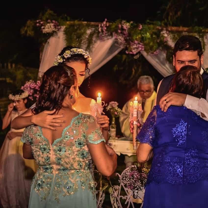 Mães dos noivos entregando velas aos filhos na cerimônia da luz.