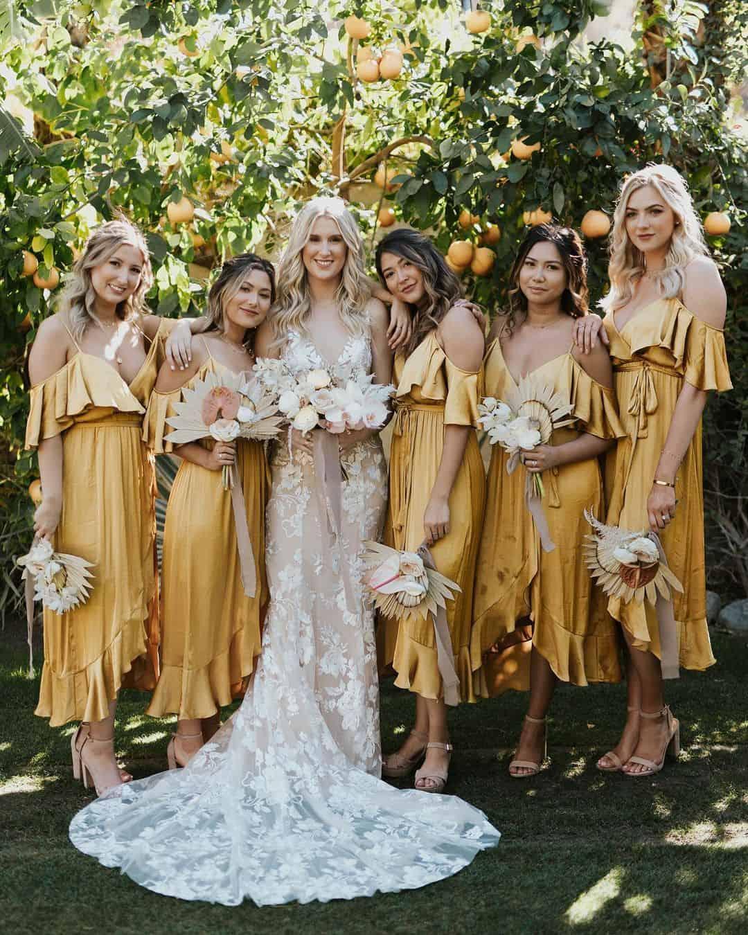 Noiva com madrinhas de vestido amarelo metálico.